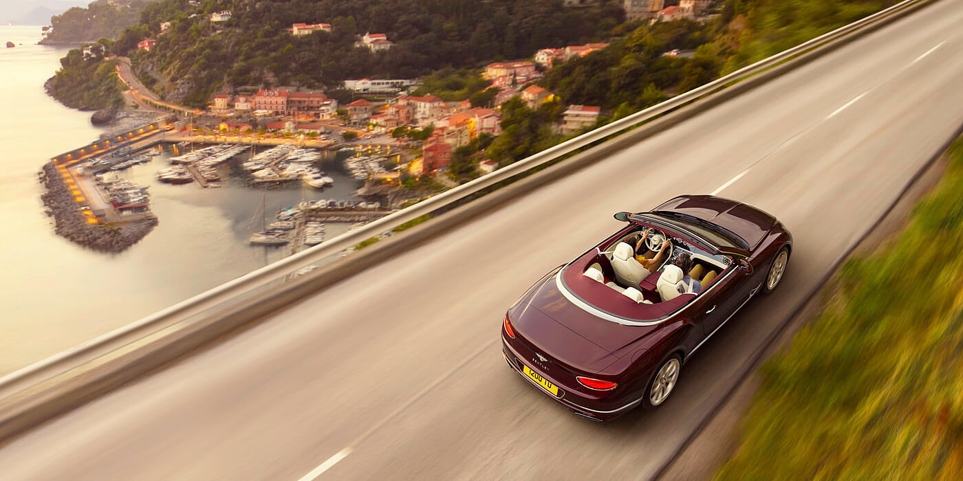 DARK-RED-BENTLEY-CONTINENTAL-GT-CONVERTIBLE-DRIVING-NEAR-ITALIAN-SEASIDE-TOWN